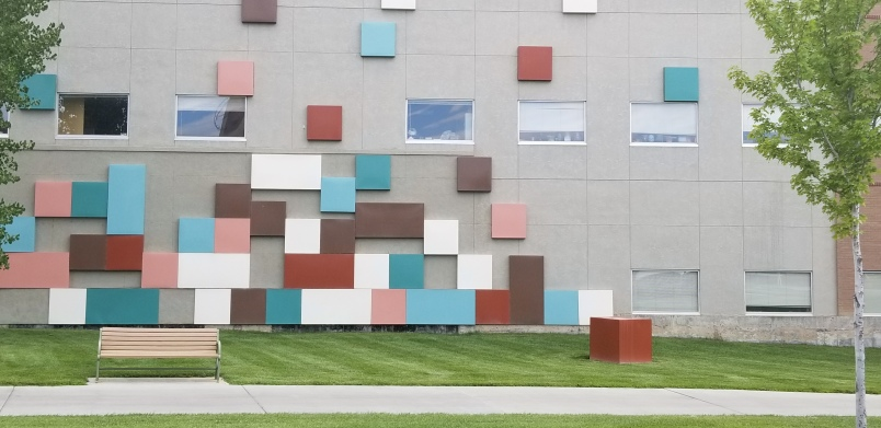 The image shows a bench in front of the side of a building which features colorful squares.