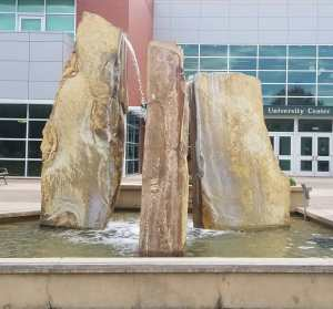 The image shows a water fountain composed of three large stones.