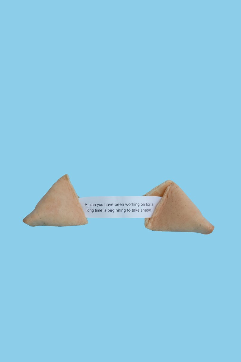An image of a split fortune cookie with a fortune that reads,