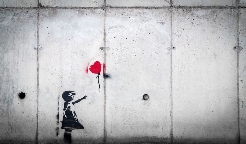 Image of a stenciled girl in black letting go of a red heart balloon