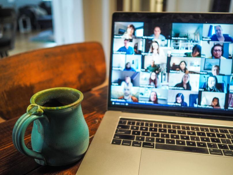 Zoom call on a MacBook Pro laptop with a green ceramic mug on the left