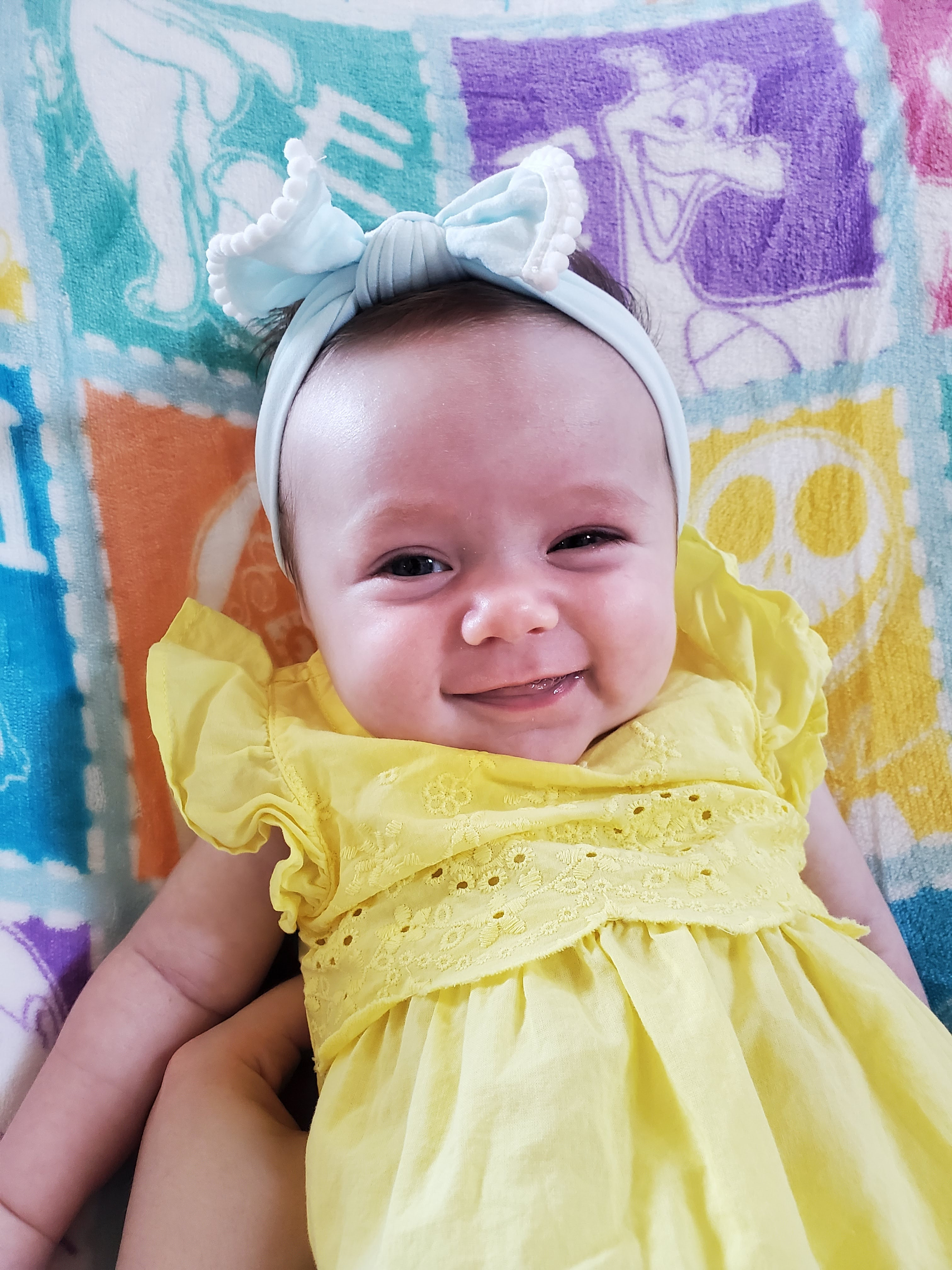 Baby wearing a yellow romper and blue headband
